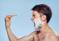 Mann schreit seinen günstigen Klingenrasierer an, da er sich geschnitten hat.